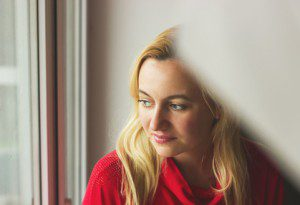 Toned portrait of Beautiful blonde woman sitting by the window.