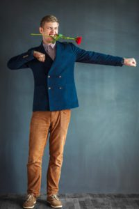 Handsome young man dancing with a red rose in his mouth against grey wall background