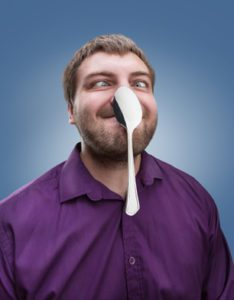 Strange adult man holds a spoon on his nose