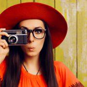 Frau mit Hut und Fotoapparat