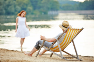 Mann im Liegestuhl am See schaut zu einer jungen Frau im Wasser