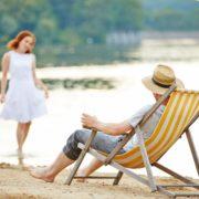 Mann im Liegestuhl schaut auf Frau, am See
