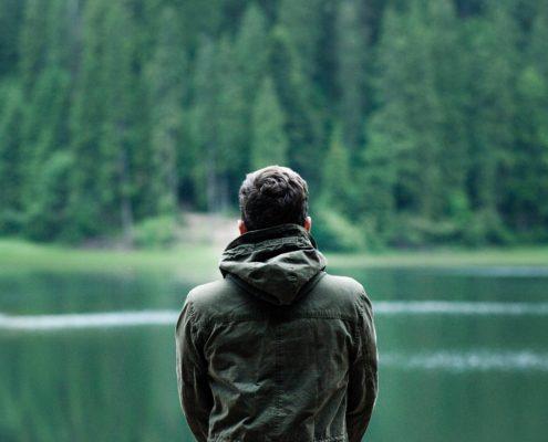 Mann sitzt am See