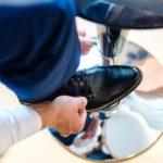 Mann mit Schuh auf Hocker