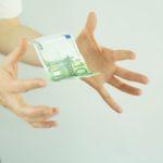 Frauenhände fangen Geld auf