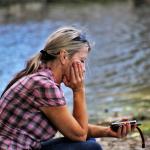 Frau mit Handy sitzt traurig am See